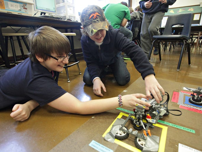Dylan Westfall, left, and Soren Blamey test the robot they made in a WINGS program robotics class at Phelps Center for the Gifted on Monday, February 3, 2014.