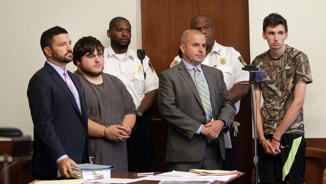 James Stumbo, second from left, and Kevin Norton, right, both of Iowa, stand in court during their arraignment at Boston Municipal Court in Boston, Monday, Aug. 24, 2015 with their lawyers Steven Goldwyn, left, and John O'Neill, Jr., second from right.  Stumbo and Norton were arrested and charged with unlawful possession of a firearm, unlawful possession of ammunition and other firearms charges after allegedly threatening the Pokémon World Championships at Hynes Convention Center in Boston.