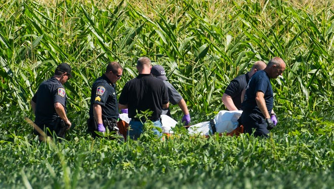 Officials remove the body of a suspect shot and killed by police in a soybean field in the village of Campbelltown in South Londonderry Township on Aug. 3, 2015. Police responded to a burglary at the Horseshoe Pike Gun Shop when they encountered the suspect and were fired upon. Police returned fire and the suspect died in a soybean field.