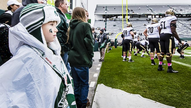 Austin Winnie (left) enthusiastically watches members of the Purdue football team warmup before last season's game in East Lansing.
