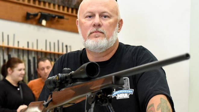 Jim Wood, a certified NRA firearms instructor, is photographed at Nuckols Gun Works where he works Thursday, August 20, 2015. Wood feels it is important for hunters to not get tunnel vision and focus only on their prey.