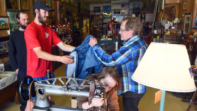 Yvonne Young works with the vintage sewing machine as Appalachian Trail thru-hiker Garrett Kreiner, aka. Yahtzee, of Greenville, S.C., hands his ripped rain coat over to David Young for repair at Graham's Shoe Repair on May 11, 2017.