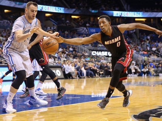 Miami Heat guard Josh Richardson (0) and Orlando Magic forward Jason Smith (14) fight for a loose ball during the first half of an NBA basketball game in Orlando, Fla., Friday, April 8, 2016. (AP Photo/Willie J. Allen Jr.)