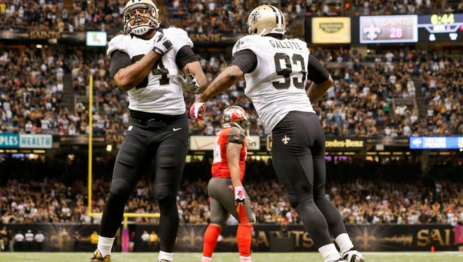 New Orleans Saints defensive end Cameron Jordan (94) and outside linebacker Junior Galette (93) celebrate following a safety against the Tampa Bay Buccaneers during the fourth quarter of a game at Mercedes-Benz Superdome. The Saints defeated the Buccaneers 37-31 in overtime.