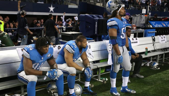 The Detroit Lions  Ezekiel Ansah, Ndamulong Suh and Darryl Tapp on the bench after the 24-20 loss to the Dallas Cowboys on Sunday, January 4, 2015 AT&T Stadium in Arlington Texas.