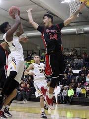 Dee Smith, left, attempts a shot while being defended by Roswell's Daniel Amador.