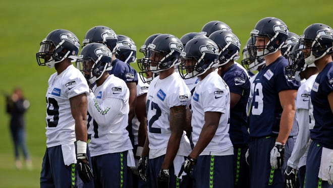Players look on while taking part in drills at Seattle Seahawks NFL football rookie minicamp Sunday, May 10, 2015, in Renton, Wash.
