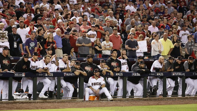 Diamondbacks players and coaches watch the ninth inning of NLDS Game 3 from the home dugout on Monday at Chase Field.