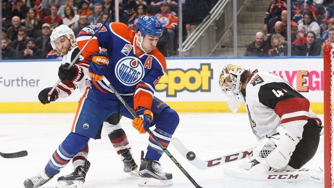 Arizona Coyotes goalie Mike Smith (41) makes the save on Edmonton Oilers' Milan Lucic (27) as Coyotes' Alex Goligoski (33) defends during second period NHL hockey action in Edmonton, Alberta, Monday Jan. 16, 2017.