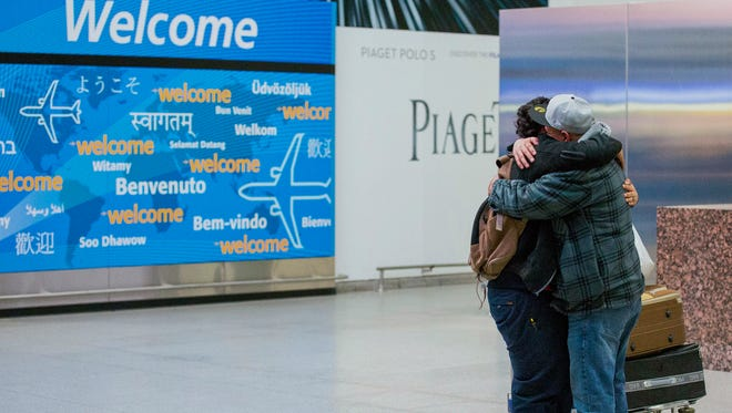 Abdullah Alghazali, right, hugs his 13-year-old son Ali Abdullah Alghazali after the Yemeni boy stepped out of an arrival entrance at John F. Kennedy International Airport in New York on Feb. 5, 2017.