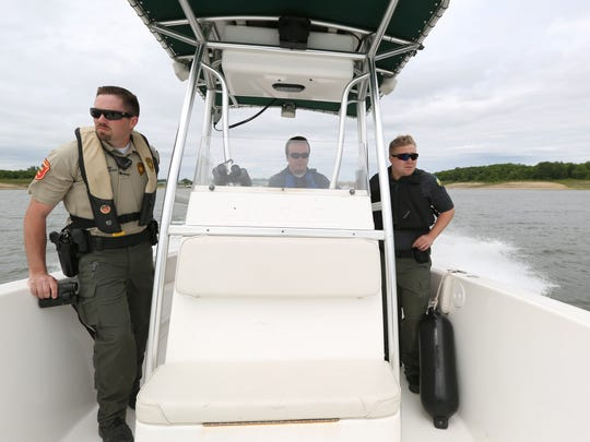 Dustin Eighmy, left, a conservation officer with the Iowa DNR, patrols watercraft on Saylorville Lake on Saturday, May 23, 2015.