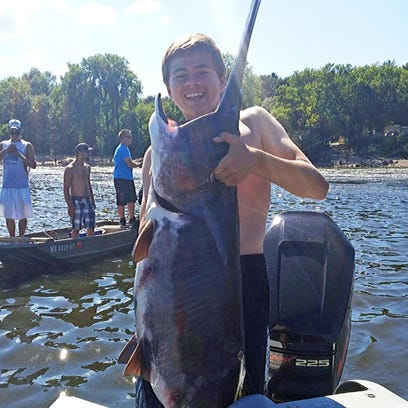 Alec Riddle, 15, of Middleton, briefly holds up a paddlefish that he and his friend Logan Thomas caught July 23 on the Wisconsin River below the dam at Prairie du Sac.