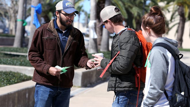 Ruben Vidaurri (left), treasurer of the Student Citizen Activists at Texas A&M University-Corpus Christi, hands out fliers for the first meeting of the organization on Wednesday, February 15, 2017.