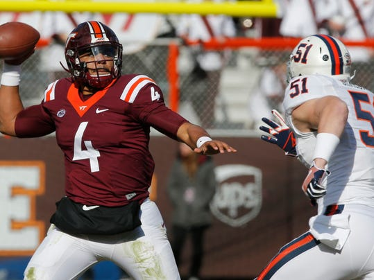 Virginia Tech quarterback Jerod Evans (4) tosses a pass as Virginia linebacker Zach Bradshaw (51) closes in during the first half of an NCAA college football game in Blacksburg, Va., Saturday, Nov. 26, 2016. (AP Photo/Steve Helber)
