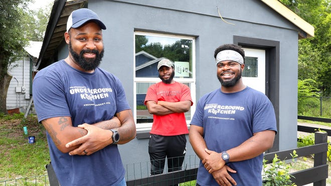 Carl Watts, left, the owner and chef of Underground Kitchen, poses with his executive sous chef Joshua Joseph, right, and Reginald Maxwell, center, a chef at the restaurant, outside the building that will be their new restaurant on Northwest Fifth Avenue in Gainesville in early June.