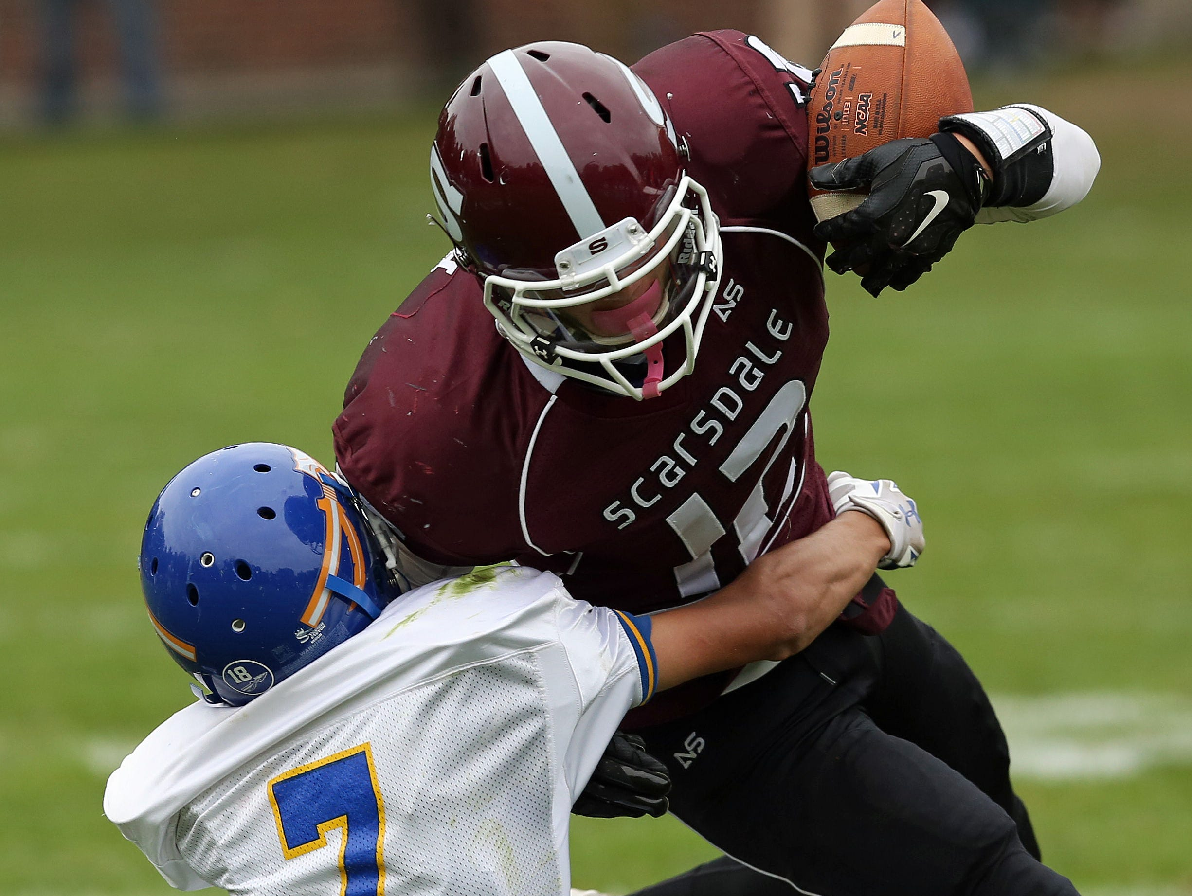 Scarsdale's Robbie Keith (12) tries to get around Mahopac's Andrew Winogradoff (7) on a second half run during football playoff game at Scarsdale High School Oct. 24, 2015. Scarsdale won the game 33-28.