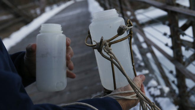 Bill Blubaugh, lab technician with Des Moines Water Works, collects water samples Jan. 15 at multiple points along the Raccoon River in Des Moines.