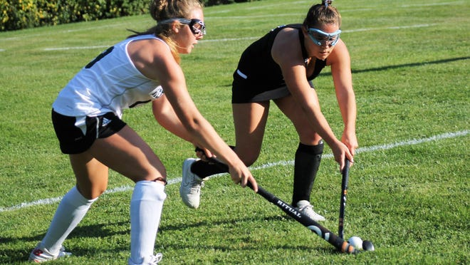 Dover's Audrey Carter, left, battles for possession with Oyster River's Nadia Pavlik during field hockey action Monday at Fisk Field in Dover.