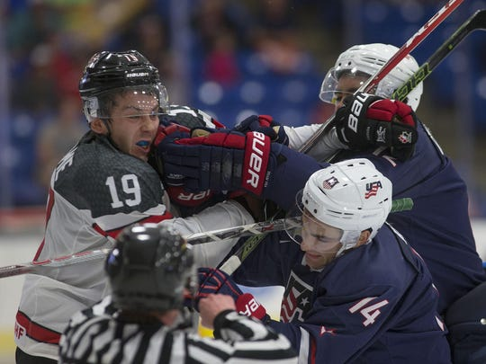 Team Canada forward Dylan Strome (No. 19) takes it on the chin from Team USA forwards Luke Kunin (No. 14) and Jordan Greenway (No. 12) during Saturday night's contest at USA Hockey Arena in Plymouth.