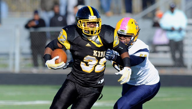 Detroit King running back Martell Pettaway runs for yardage as he is chased by Detroit East English Village's Orniska Webster in the first quarter.