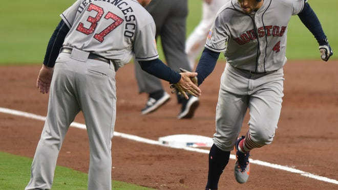 Houston Astros' George Springer celebrates a run with Astros Triple-A manager Tony DeFrancesco during the third inning of a baseball game against the Atlanta Braves, Tuesday, July 4, 2017, in Atlanta. (AP Photo/Richard Hamm)