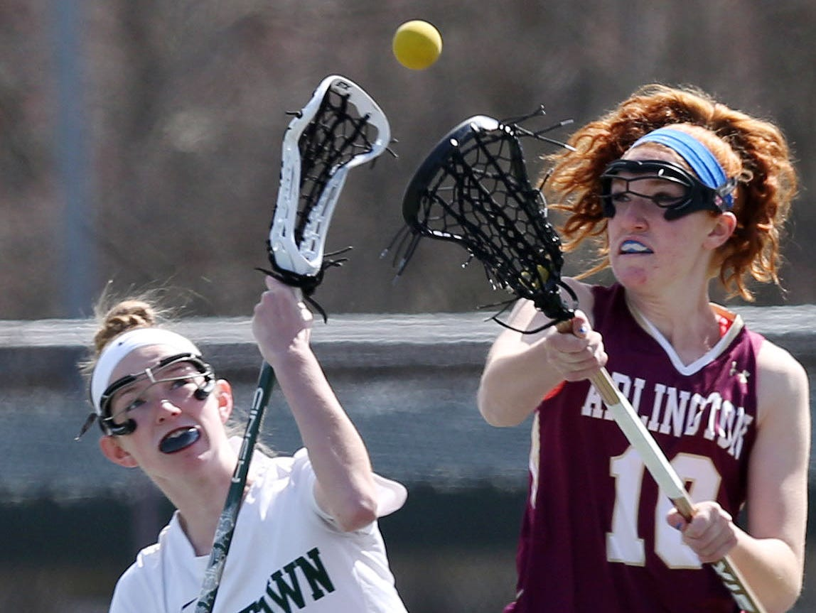 From left, Yorktown's Ciara Frawley (5) and Arlington's Abby Carlin (10) battle for ball control during girls lacrosse action at Yorktown High School March 26, 2016. Yorktown won the game 14-5.