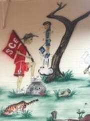A mural on the gym wall of South Cumberland Elementary School in Crossville, Tenn., has been modified to show a figure in a rival school uniform no longer hanging by his jersey from a tree branch. Confederate battle flags also were revised.