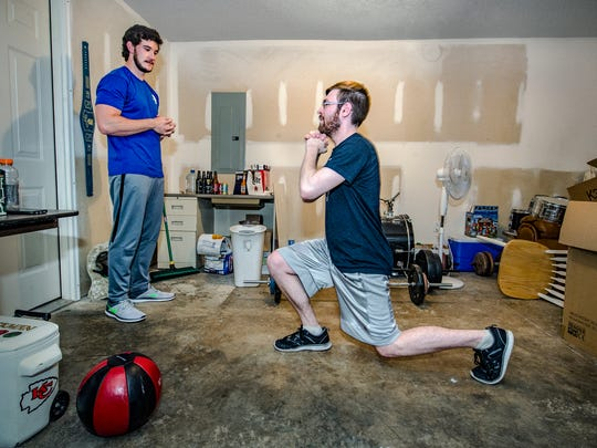 Performance coach Jake Middleton, left, helps client Mat Smith with exercises on November 29, 2016, in Smith's Grain Valley, Mo., home. Smith is captain of Team KC, an amateur competitive video gaming group, and the team is learning how to exercise for their sport.
