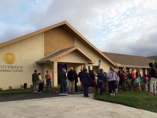 Faculty, parents and students watch the ribbon cutting, opening the new addition at Providence Christian School in Cape Coral.