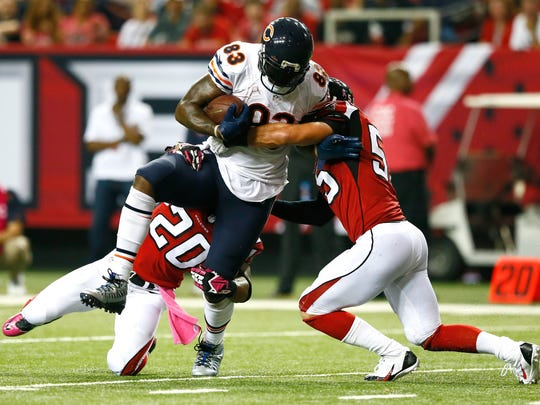 ATLANTA, GA - OCTOBER 12:  Martellus Bennett #83 of the Chicago Bears pulls in this reception against Dwight Lowery #20 and Paul Worrilow #55 of the Atlanta Falcons at Georgia Dome on October 12, 2014 in Atlanta, Georgia.  (Photo by Kevin C. Cox/Getty Images)
