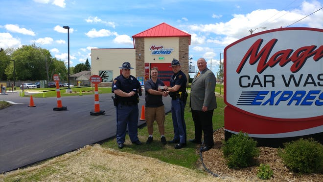 Magic Car Wash of Sheboygan and Manitowoc recently madea $1,200 donation to the Wisconsin State Patrol. Pictured are Steve Benish, president of Magic Car Wash, handing the donation to Capt. Ryan Chaffee, along with Sgt. Andrew Hyer and Pastor John Putnam, in front of Magic Car Wash Express in Manitowoc.