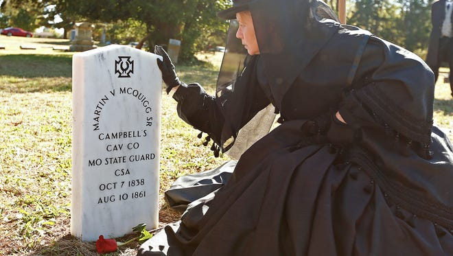 Janet Sing, who attended the event in period mourning attire, touches the tombstone of Confederate soldier Martin Vanburen McQuigg during a ceremony honoring the McQuigg with a new grave marker at Brick Chuch Cemetery in Springfield, Mo. on Oct. 22, 2016.