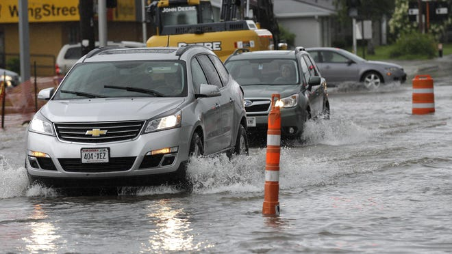 Motorists try to drive through rising water levels Monday at the corner of Meade Street and Northland Avenue in Appleton.