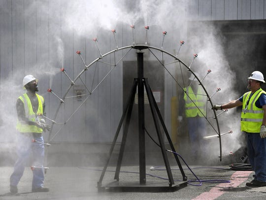 In this April 29, 2019 photo, workers test a spray to be used for controlling contaminated dust in the decommissioning process at Vermont Yankee Nuclear Power Station in Vernon, Vt. In January, privately held NorthStar Group Services completed the purchase of Vermont Yankee from New Orleans-based Entergy after federal and state regulators approved the sale of the reactor, closed since 2014. It marked the first permanent transfer of an operating license to a nuclear cleanup specialist for accelerated decommissioning. (AP Photo/Jessica Hill)
