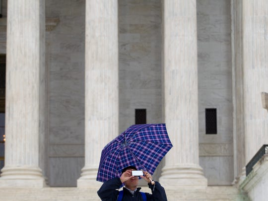 A visitor takes photos with his cellphone outside the Supreme Court in April, when the justices considered whether police may search cellphones during arrests.