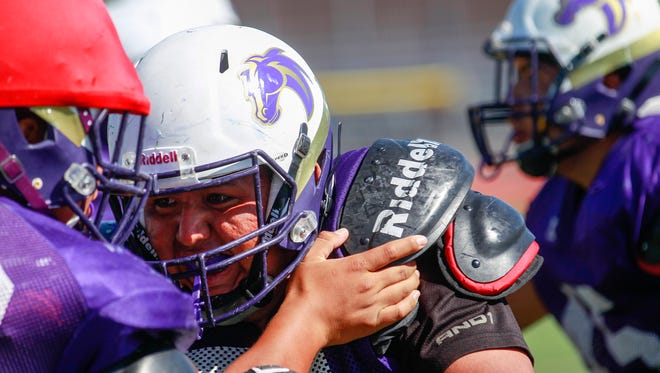 Kirtland Central's Tryell Clyde blocks during team practice on Wednesday, Aug. 17, 2017 at Bronco Stadium in Kirtland.