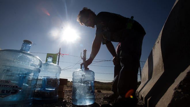 Justin Krumwiede fills water jugs Friday at a drinking water fill station in the Harvest Gold subdivision.