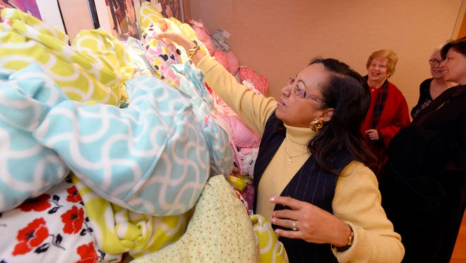 Zonta Club of the Michigan Capitol Area member Bettye Gilkey stacks pillows with Zonta Club of Lansing and Zonta Club East Lansing Area members as the Zonta Members donate 285 handmade support pillows for recovering mastectomy patients at Sparrow Cancer Center in Lansing Thursday 12/11/2014.