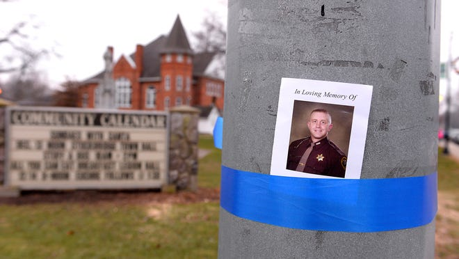 Memorials in Stockbridge on the way to the funeral for Ingham County Sheriff's Deputy Grant Whitaker in December.