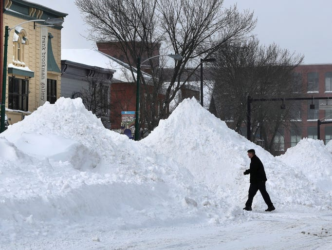 A man crosses Maine Street where snow has been piled