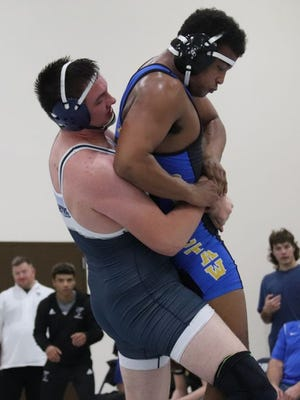 Shawnee's Lane Williams, competing at 220 pounds, bear hugs Choctaw's Zavier Smith during action Tuesday night at the new Stucker Wrestling Complex.     PHOTO BY BRIAN JOHNSON