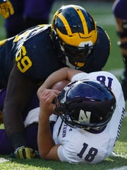 Oct 10, 2015; Ann Arbor, MI, USA; Northwestern Wildcats quarterback Clayton Thorson (18) is sacked by Michigan Wolverines defensive tackle Willie Henry (69) in the second quarter at Michigan Stadium.