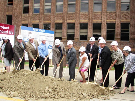 Local officials and business leaders take part in a formal groundbreaking ceremony Thursday for a project to convert the former Corning Free Academy Middle School into upscale apartments.