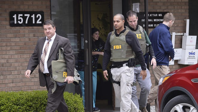 FBI agents leave the office of Dr. Fakhruddin Attar at the Burhani Clinic in Livonia Friday morning after completing a search for documents.