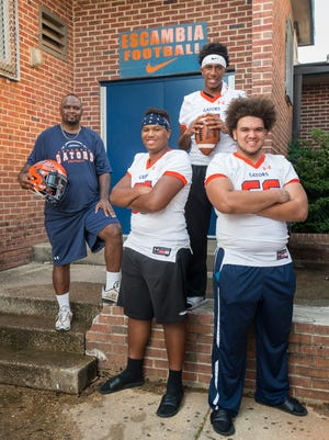 Assistant football coach Reggie Smith Sr., left, poses with his grandsons, left to right, offensive lineman Jalen Smith, quarterback AV Smith, and offensive lineman Reggie Smith III at Escambia High School in Pensacola on Thursday.
