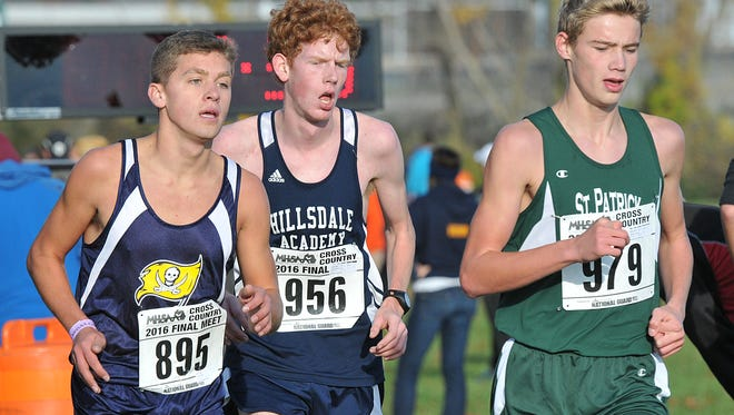 Pewamo-Westphalia's Bryce Thelen, left, is on his way to a 7th place finish at the MHSAA LP Cross Country Finals Saturday, October 5, 2016. Hillsdale Academy senior Noah Heckenlively, center, and Portland St. Patrick's Ashton Walker match strides. Pewamo-Westphalia's team won the Division 4 boys state title.
