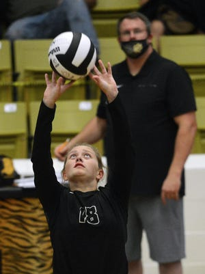 Charleston's Jordan Sims sets the ball as coach Ryan Rachuy looks on during the second set against Lincoln on Thursday, Sept. 24 at Charleston.