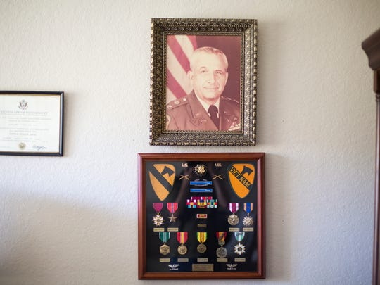 A photo and medals hang on a wall of Army veteran William Bramblet's home office in North Naples.