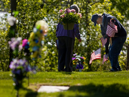 American Legion Post 449 member Jim Vokes, of Marysville, places a flag at the grave of a veteran Saturday at Riverlawn Cemetery in Marysville.