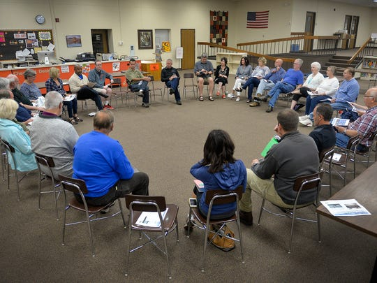 Community members, neighbors, school district officials, construction representatives and St. Cloud Mayor Dave Kleis gather in a circle inside the school media center Saturday, Sept. 17, 2016, to discuss the future of Technical High School.